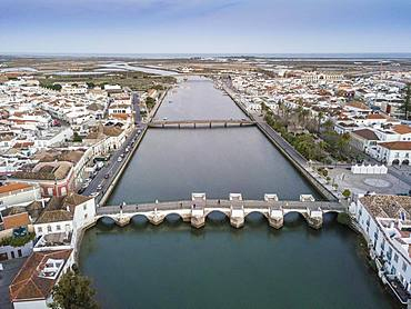 City view with roman bridge over Gilao river in old fishermen's town, Tavira, drone shot, Algarve, Portugal, Europe