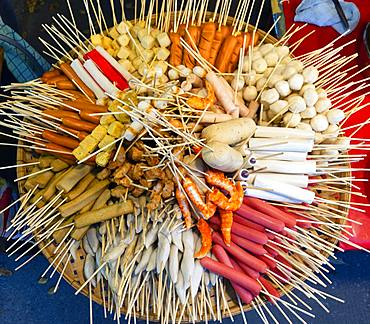 Various skewers with sausage and meat, meatballs, in bamboo basket at a market, Thai cuisine, Thailand, Asia