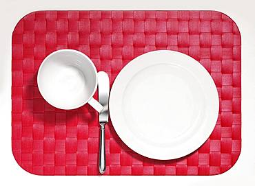 Cover, empty white plate and cup, knife on red placemat, optional, Germany, Europe