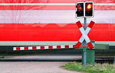 Train passes level crossing with barrier, near Loebejuen, Saxony-Anhalt, Germany, Europe