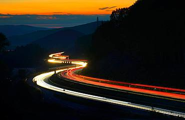 A3 motorway meanders through low mountain range landscape, light tracks at dusk, Spessart, Bavaria, Germany, Europe