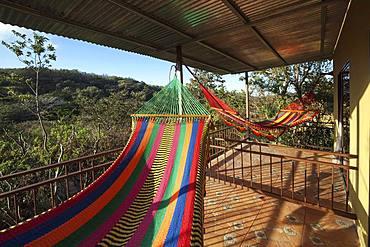 Colourful hammocks on the terrace, Rinconcito Lodge at Rincon de la Vieja National Park, near Liberia, Guanacaste Province, Costa Rica, Central America