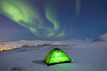 Green illuminated tent in the snow and aurora borealis above Fjellheisen, Tromsoe, Norway, Europe