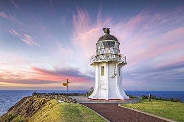 Lighthouse with signpost at Cape Reinga at sunset with pink clouds, Far North District, Northland, North Island, New Zealand, Oceania