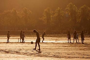 Young people playing football on the beach, evening light, Playa Samara, Samara, peninsula Nicoya, province Guanacaste, Costa Rica, Central America