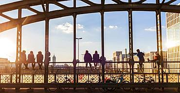 Young people sitting on the balustrade of the Hackerbruecke bridge over the railway tracks and looking into the distance, back light, Munich, Upper Bavaria, Bavaria, Germany, Europe