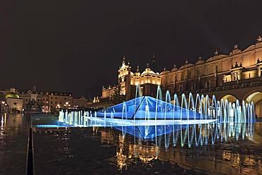 Illuminated fountain with cloth halls at night, market square, Krakow, Poland, Europe