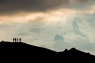Silhouette of tourists at the ridge with view of Hvannadalshnukur and glacier Oeraefajoekull, South Iceland, Iceland, Europe