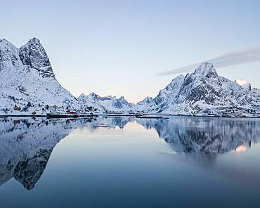 Snow-covered mountains reflected in fjord, sunrise, drone shot, Reine, Lofoten, Norway, Europe