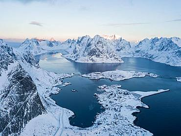 Snow-covered mountains at the fjord with place Reine, sunrise, drone shot, Lofoten, Norway, Europe