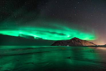 Northern Lights (Aurora Borealis) with starry sky at the beach, drone shot, Flakstad, Lofoten, Norway, Europe