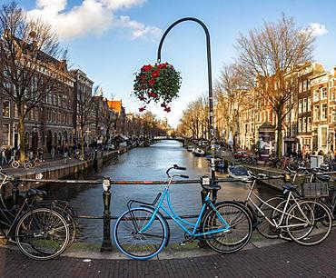 Parking bicycle on bridge over canal at Oudezijds Voorburgwal, behind Sint Nicolaaskerk, Sankt Nikolas church, Amsterdam, North Holland, Netherlands