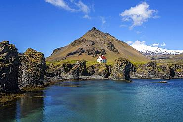 Lonely house on the basalt coast near the harbour, behind the mountain Stapafell and the glacier Snaefelljoekull, Arnarstapi, peninsula Snaefellsness, Iceland, Europe