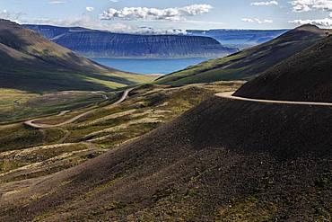 Gravel road meanders through volcanic landscape, near Hrafnseyri, Westfjords, Iceland, Europe
