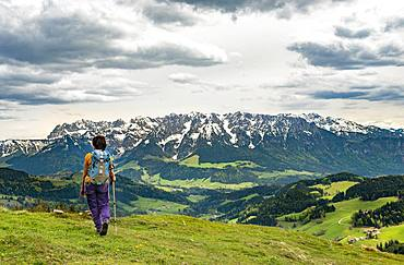 Female hiker on the hiking trail to Spitzstein, at the back mountain range Zahmer Kaiser with snow, Erl, Austria, Europe