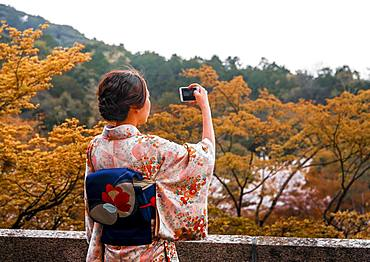 Japanese woman dressed with kimono, photographed with a mobile phone, at Kiyomizu-dera Temple, Higashiyama, Kyoto, Japan, Asia