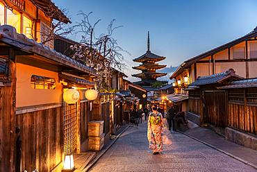 Woman in kimono in a lane, Yasaka dori historical alleyway in the old town with traditional Japanese houses, behind five-storey Yasaka pagoda of the Buddhist Hokanji temple, evening mood, Kyoto, Japan, Asia