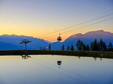 Alpine panorama, gondola of the Jennerbahn cable car reflected in the evening light in an artificial mountain lake, Jenner, Berchtesgadener Alps, Schoenau am Koenigssee, Berchtesgadener Land, Upper Bavaria, Bavaria, Germany, Europe