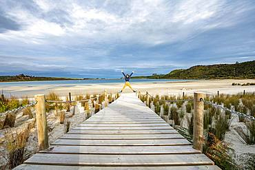 Young man jumps, boardwalk to the beach, Taharoa Lake, Northland, North Island, New Zealand, Oceania