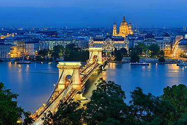Chain bridge with Gresham Palace and St. Stephen's Basilica, illuminated, dusk, Budapest, Hungary, Europe