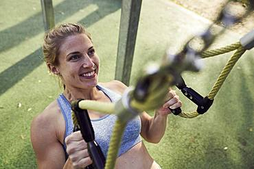 Sporty young woman doing fitness training on the rings, outdoor sports, sporty, Olympiapark, Munich, Germany, Europe