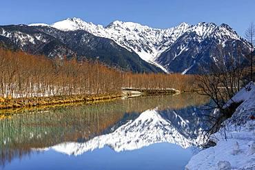 Snow-covered mountains at a lake, Japanese Alps reflected in Taisho Pond, snow-covered Mount Hotaka at the back, Kamikochi, Matsumoto, Nagano, Japan, Asia