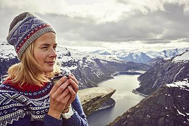 Young woman in Norwegian sweater drinks tea, enjoys view over Trolltunga, Norway, Europe