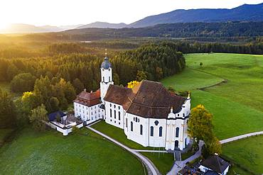 Wieskirche at sunrise, pilgrimage church to the Scourged Saviour on the Wies, Wies, near Steingaden, Pfaffenwinkel, aerial view, Upper Bavaria, Bavaria, Germany, Europe