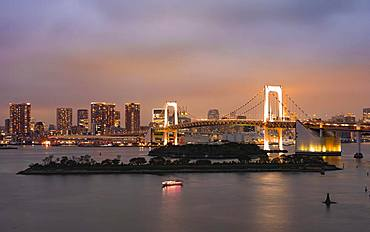 View of skyline with skyscrapers and illuminated Rainbow Bridge in the evening, Odaiba, Tokyo, Japan, Asia