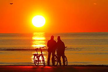 Couples with bikes on the beach watching the sunset, North Sea, St. Peter-Ording, North Sea coast, Schleswig-Holstein Wadden Sea National Park, Schleswig-Holstein, Germany, Europe