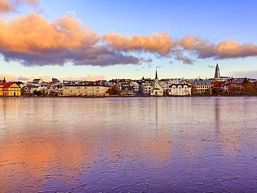 Frozen lake Tjoernin in the city centre, cloud reflection at sunset, Reykjavik, Iceland, Europe