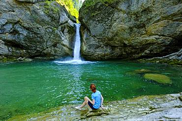 Young woman sitting in front of Buchenegger waterfalls near Oberstaufen, Oberallgaeu, Allgaeu, Swabia, Bavaria, Germany, Europe