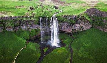 Aerial view, Seljalandsfoss waterfall falls from high cliff, green grass landscape, South Iceland, Iceland, Europe