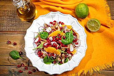 Served salad on a porcelain plate with orange slices, pomegranate, rocket and oyster mushrooms, on a wooden desk and fabric, food, Russia, Europe