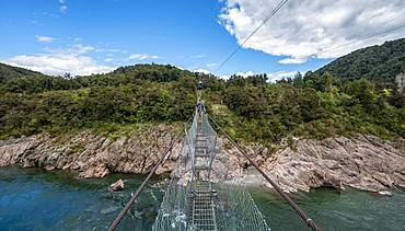 Young man on suspension bridge over Buller River, Buller Gorge Swing Bridge, Inangahua, West Coast, South Island, New Zealand, Oceania