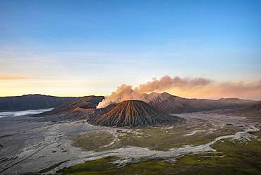 Volcanic landscape at sunrise, smoking volcano Gunung Bromo, with Mt. Batok, Mt. Kursi, Mt. Gunung Semeru, Bromo-Tengger-Semeru National Park, Java, Indonesia, Asia