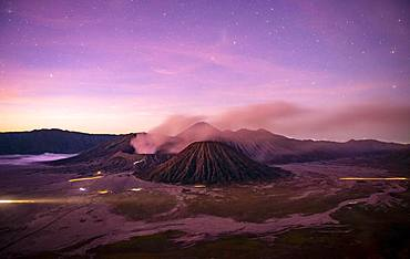Volcanic landscape at sunrise with starry sky, smoking volcano Gunung Bromo, with Mt. Batok, Mt. Kursi, Mt. Gunung Semeru, National Park Bromo-Tengger-Semeru, Java, Indonesia, Asia