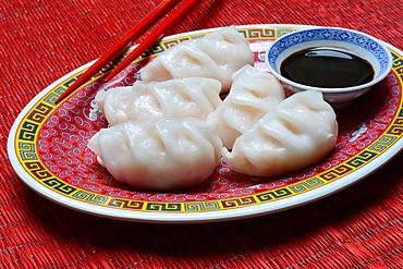Dim Sum, filled dumplings on plate with chopsticks and soy sauce, Germany, Europe