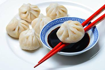Dim Sum, filled dumplings and bowl with soy sauce, red chopsticks, Germany, Europe