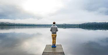 Young man standing on a jetty looking over a lake, foggy atmosphere, Lake Mapourika, West Coast, South Island, New Zealand, Oceania