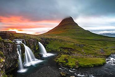 Waterfall Kirkjufellsfoss and mountain Kirkjufell, sun breaks through clouds, Grundarfjoerdur, Snaefellsnes peninsula, Snaefellsnes, Vesturland, Iceland, Europe