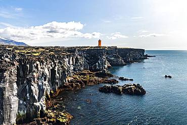 Orange lighthouse of Oendverdarnes stands on cliffs, lava rocky coast, Oendveroarnes, Snaefellsjoekull National Park, Snaefellsnes Peninsula, Snaefellsnes, Vesturland, Iceland, Europe