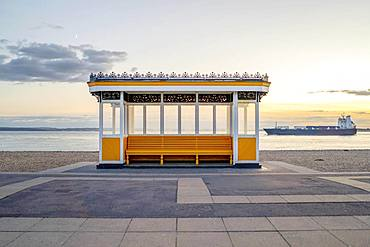Yellow vintage bus stop by the sea in Portsmouth, Great Britain