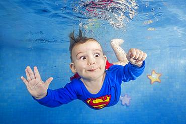 Little boy in a superman costume dives underwater in the pool, front view, Ukraine, Europe