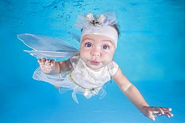 Little girl in fairy costume dives underwater in a swimming pool