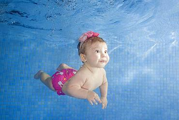 Little baby learning to swim underwater in a swimming pool, Ukraine, Europe