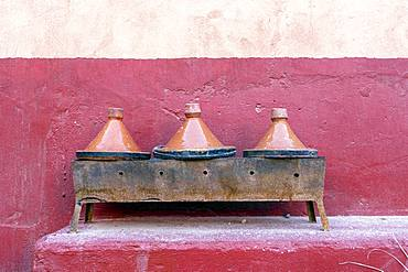 Three clay tagine pots on portable barbeque, Morocco, Africa