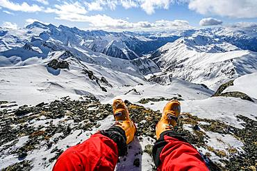 View from the summit of the Geierspitze, legs with ski boots in front of a snow-covered mountain panorama, Wattentaler Lizum, Tuxer Alps, Tyrol, Austria, Europe