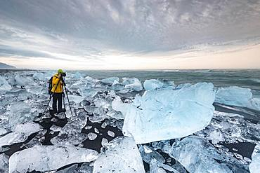 Photographer at Diamond Beach, icebergs at the black lava beach, near glacier lagoon Joekulsarlon, Vatnajoekull National Park, Hornafjoerour, Southern Iceland, Iceland, Europe