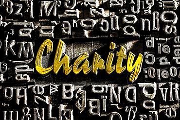 Old lead letters with golden writing show the word Charity, Germany, Europe